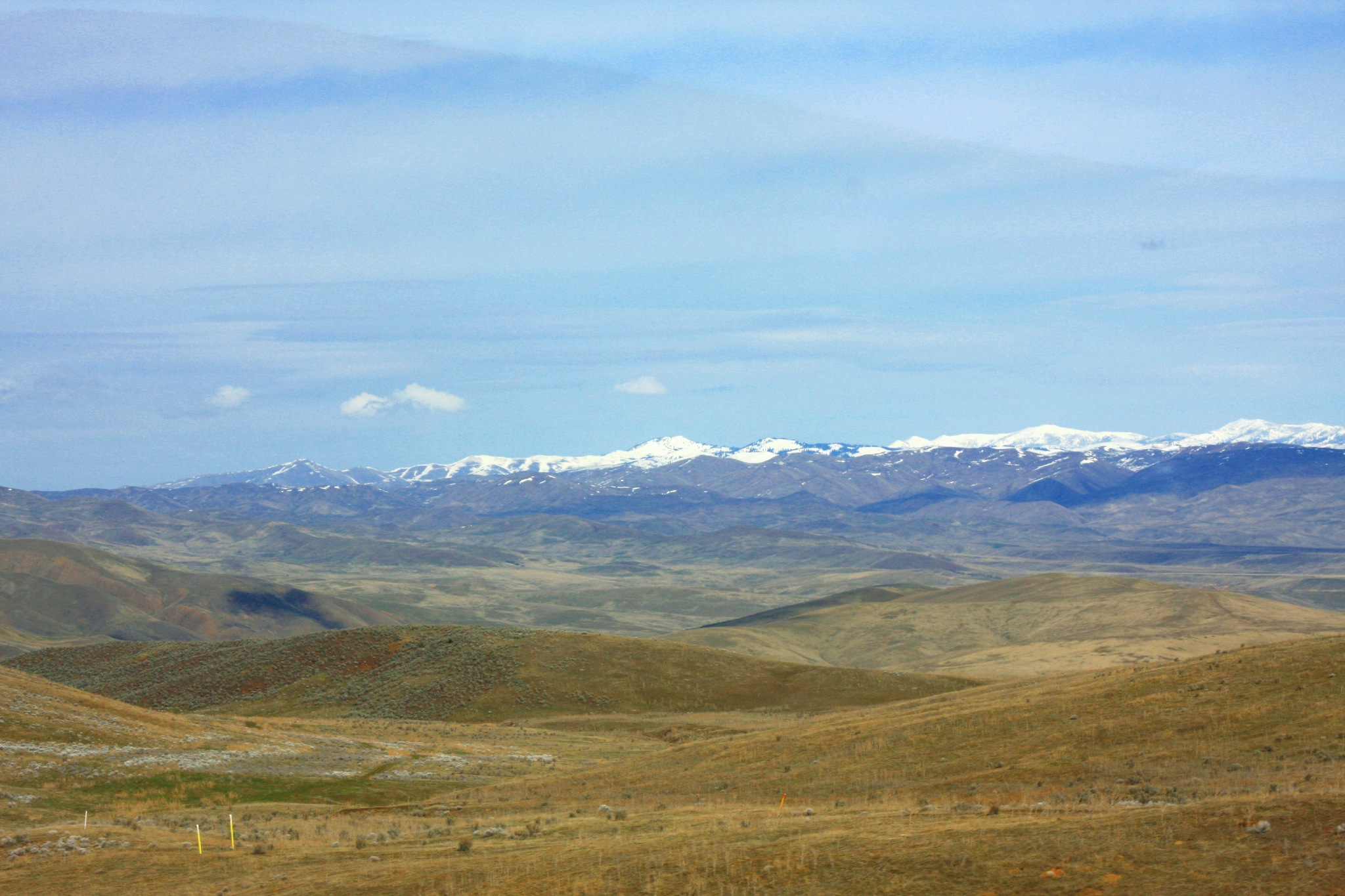 Snowcapped Peaks In The Distance With Rolling Hills Foreground