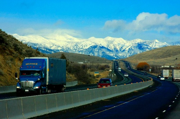 Trucks On The Freeway Snowcapped Peaks In Background